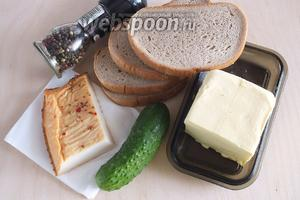 Подготовьте необходимые ингредиенты: копчёный кальмар, серый хлеб, сливочное масло комнатной температуры, свежие огурцы и немного чёрного перца.