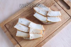 На 4 кусочка хлеба выложите кусочки кальмара, чуть поперчите.