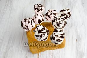 Украсить шарики каплями растопленного шоколада. Удобно перед украшением нанизать их на шпажки, а потом воткнуть в корочку хлеба. Убрать в морозилку для застывания.