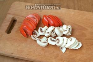 Тонкими дольками нарезать помидоры и пластинками шампиньоны.