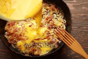 Залить яйцами, румяный лучок. Готовить на плите или в духовке, до желаемой готовности. Накрыть тарелкой сковороду и перевернуть.