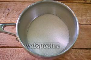 В кастрюлю с толстыми стенками поместите 2 стакана сахарного песка. Поставьте на огонь. Помешивая, доведите сахар до состояния карамели. Он должен стать коричневым.