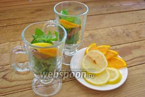 В каждую чашку помещаем дольку апельсина и лимона.