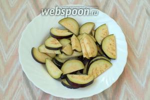 У баклажанов удалить плодоножку и нарезать полукругами толщиной 5 мм. Посолить и оставить на 30 минут.