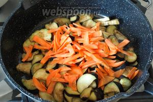 В сковороде разогреть подсолнечное масло. С баклажанов слить жидкость и выложить их в сковороду, добавить морковь.