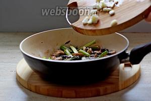 В сковороду к шампиньонам добавить спаржу, готовить 3 мин. Затем добавить чеснок и жарить ещё 1 мин.