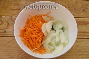 В миску к базилику помещаем морковь. Полукольцами нарезаем репчатый лук.
