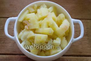 Отварите картофель в мундире. Очистите и нарежьте кубиком.