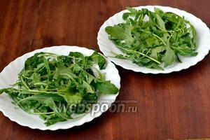На тарелки кладём вымытую и обсушенную рукколу.