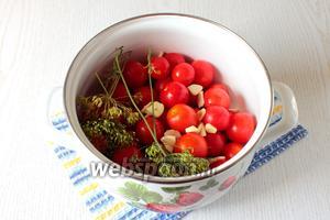 Подготовленные помидоры уложите в кастрюлю. Добавьте к помидорам перец горошком, нарезанный пластинками чеснок, веточки укропа и лавровый лист.