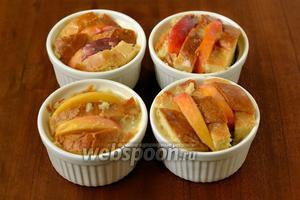 Укладываем в порционные чашечки булку, чередуя её с дольками персиков. Остатки яично-сливочной смеси можно добавить в чашечки.