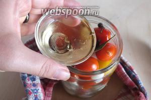 Снимите крышку-ситечко и влейте в банку к помидорам уксус. Затем залейте закипевшим маринадом ещё раз.