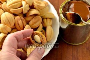 Готовые скорлупки наполняем варёной сгущёнкой и в середину кладём орешек. Я использовала миндаль. Соединяем половинки, чтобы получить целые орешки.