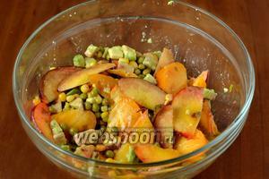 Складываем в общую посуду кукурузу, зелёный горошек, авокадо, персик, помидор, вливаем соус, двумя осторожными движениями снизу вверх смешиваем.