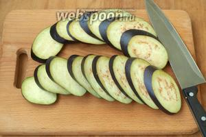 У баклажанов удалить плодоножку и нарезать наискосок кругами, толщиной 7 мм.