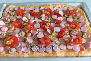 На тесте разложить сначала сосиски, затем помидоры, затем оливки. Помидоры немножко присолить, кто любит посолонее, то можно слегка присолить всю начинку.