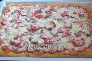 Поставить пиццу в заранее разогретую до 180ºC духовку на 25-30 минут. Для проверки продавите пальцем корочку, если она возвращается на место, то пицца готова.  Пицца по-домашнему готова. Подавать с острым оливковым маслом и газировкой. Приятного аппетита!
