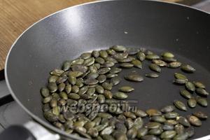 Тыквенные семечки обжарить на сухой сковороде, выложить на тарелку и дать остыть.