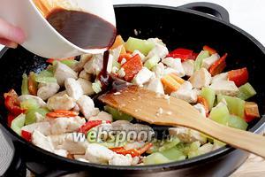 Влить соус-маринад. Опять хорошо размешать содержимое сковороды. Жарить помешивая до красивой глазировки кусочков курицы. По желанию, можно на этом этапе слегка посыпать курицу крахмалом.