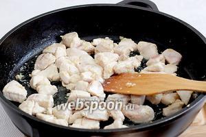 Добавить кусочки курицы и жарить помешивая, пока курица станет ровного белого цвета.