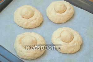 Оставшееся тесто разделить на 4 равные части, по 190 г каждая. Скатать тесто в шары, выложить на противень застеленный пергаментом. Стаканом сделать углубления по центру и вложить мелкие шарики.