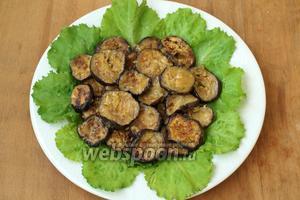 На плоскую тарелку выложить салатные листья, сверху выложить баклажаны в несколько слоёв.