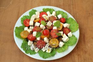 Сверху баклажанов выложить половинки помидоров и кубики сыра, полить оставшейся заправкой и по желанию посыпать перцем из мельницы. Подавать салат сразу. Приятного аппетита!