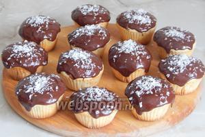 Когда шоколад немного схватится, украшаем кокосовой стружкой. Если посыпать ещё тёплый шоколад, стружка утонет в него и перестанет быть белоснежной. Кокосовые маффины с шоколадной начинкой готовы — угощайтесь!
