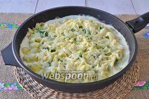 Когда яйцо начнёт запекаться, но будет ещё жидким в середине, высыпать вторую половину тёртого сыра и поместить сковороду в духовку под гриль до зарумянивания.
