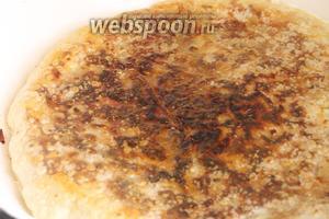 Кладём большую тарелку или широкую крышку на пирог, переворачиваем так, чтобы пирог оказался на тарелке (или крышке), наливаем ещё 1 ст. л. масла в сковороду, а потом плавно, аккуратно перекладываем пирог необжаренной стороной на сковороду. Ждём ещё 3-4 минуты, пока пирог не обжарится снизу.