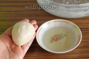 Обминаем один раз. Теперь рядом кладём тарелку с растительным маслом, обильно обмакиваем пальцы рук в масло, отрываем от теста маленький кусочек, размером с небольшую сливу, и скатываем его в шар. Кладём шарик теста в форму, смазанную маслом (форма 24 см). Так поступаем со всем тестом, каждый раз обмакивая пальцы в масло.