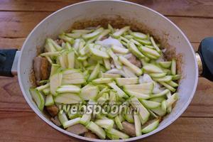 К обжаренному мясу добавьте нарезанный лук и кабачки.