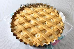 Из оставшегося теста раскатайте прямоугольник, толщиной примерно 5 мм, и нарежьте полоски. Полоски уложите на пирог в виде решётки.