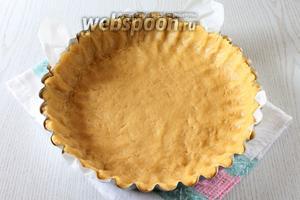 Чтобы пирог было удобнее доставать, застелите форму (диаметр 28 см) двумя полосками пергамента. Распределите по форме тесто — ту часть, которая побольше.