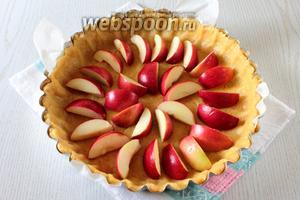 Яблоки нарежьте дольками и удалите сердцевину. Выложите яблоки на тесто.