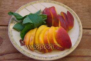 Слегка остудите готовые ленивые ватрушки. Мятные листики снять с веточек. Персик отделить от косточки и нарезать на ломтики.