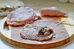 На край каждого отбитого куска мяса выложить  грибную начинку.