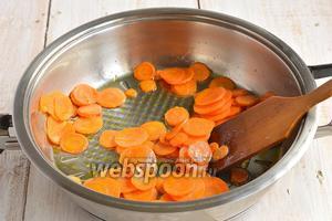Морковь очистить и нарезать очень тонкими кружками. Лучше для этого воспользоваться специальной тёркой. Обжарить на растительном масле на протяжении 5 минут, постоянно помешивая. До золотистости не доводить.