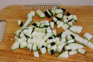 Тем временем подготовить овощи: порезать кубиками цукини.
