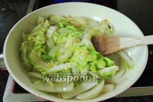 Нарежем капусту и добавим к луку в сковороду, и обжарим вместе ещё около 1 минуты.