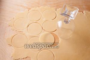 Раскатайте тесто и вырежьте из него кружочки кромкой бокала для вина. Размеры бокала роли не играют, но крупные пирожки, конечно, делать удобнее. Обладатели прижимных формочек для изготовления пирожков и пельменей могут использовать их.