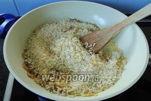 Добавляем в лук рис. Обжариваем также, мешая постоянно, до момента, когда рис становится прозрачным.
