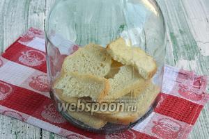 На дно чистой трёхлитровой банки выложить белый хлеб.
