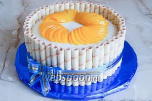 По центру торта выкладываем персики, немного приплющивая их, и оставляем место в самой серединке для винограда.