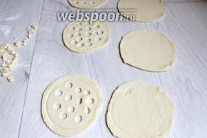 Раскатаем тесто в пласт, вырезаем такие вот кружки, чуть больше нашего горшочка. В одной части кружков вырезаем колпачком от ручки такие вот дырочки, другую оставляем чистой.