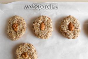 Формируем печенье и выкладываем его на противень, застеленный пергаментной бумагой. Украшаем орешками и ставим в разогретую духовку на 15 минут.