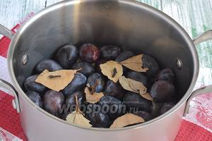 В кастрюлю выложить слоями сливы, пересыпая их лавровым листом и гвоздикой.