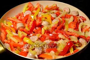 Добавляем перец к лук с колбасками, сюда же кладём помидоры, нарезанные небольшими кусочками, солим, тушим под крышкой до готовности.
