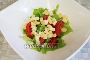 Кубиками порежем сыр и добавим в салатник.