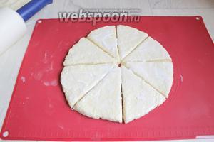 Раскатываем тесто в круг. Можно прямо на бумаге или на коврике. Можно просто распределить тесто руками. Толщина 2 см. И режем его на 8 частей. То же самое делаем с другой частью. Смажем верх кефиром. Ставим в духовку, разогретую до 200°С, на 20 минут.
